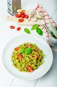 stock photo of pesto sauce  - Spinach tagliatelle with basil pesto and mini tomatoes wood board napkins and pesto mortar - JPG