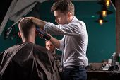 foto of clippers  - hairdresser  cuts    hair  with hair clipper on back of the head of handsome satisfied  client in  professional  hairdressing salon low angle - JPG