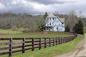 picture of dirt road  - A rustic fence and dirt road by an old Victorian home under an overcast sky in the early spring - JPG