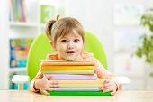 image of preschool  - Cute kid girl preschooler with books indoor - JPG