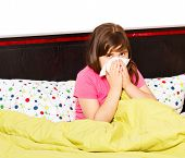 stock photo of influenza  - Little schoolgirl staying in bed because of seasonal influenza - JPG