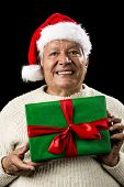 image of coy  - Shyly grinning old gentleman with a red Santa Claus cap and white knitted pullover - JPG