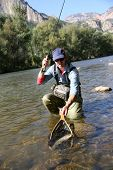 foto of fly rod  - Fly fisherman catching a fario trout in river - JPG