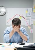 pic of nervous breakdown  - Desperate office worker with head in hands and negative financial chart on background - JPG