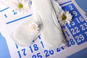 picture of menses  - Sanitary pads and white flowers on blue calendar background - JPG