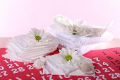 stock photo of menses  - Sanitary pads and white flowers on red calendar on pink background - JPG