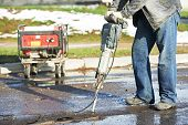 stock photo of hammer drill  - Builder worker with pneumatic hammer drill equipment breaking asphalt at road construction site - JPG