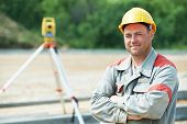 stock photo of geodesic  - One surveyor worker working with theodolite transit equipment at road construction site outdoors - JPG