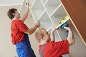 foto of assemblage  - Two carpenters workers joint and settle home built - JPG