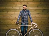 picture of biker  - Hipster man with his bike on a wooden background - JPG