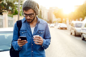 stock photo of candid  - Outdoor portrait of modern young man with mobile phone in the street - JPG