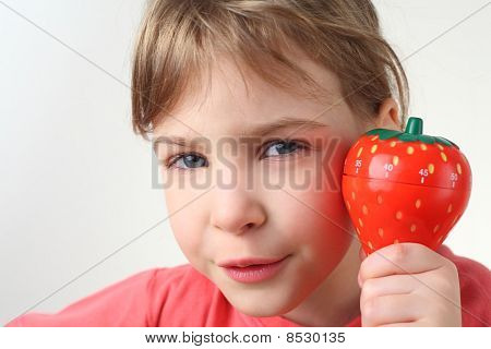 Little  Girl In Red Shirt Holding In Hand Plastic Kitchen Timer Strawberry And Looking At Camera