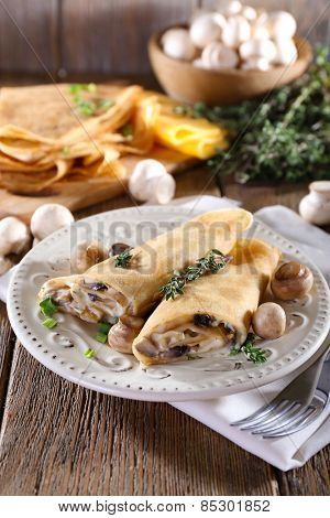 Pancakes with creamy mushrooms in plate on wooden background