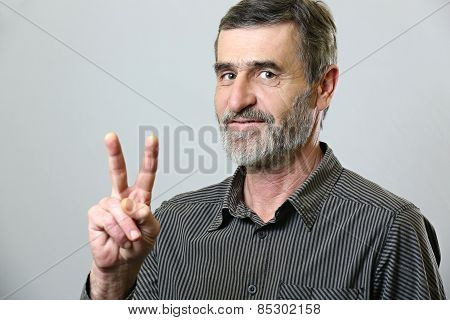 Senior man showing victory sign