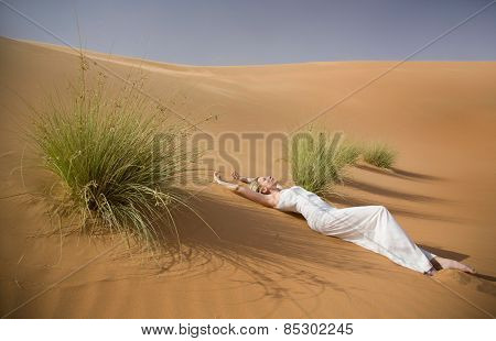Beautiful sexy woman lays in whte dress between tuffets in sand desert
