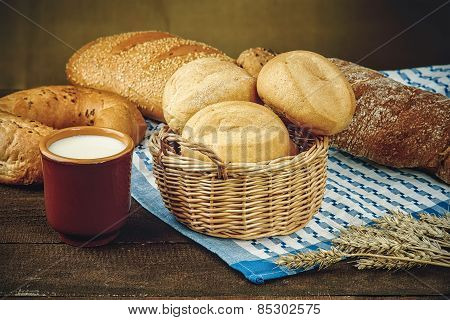 Wicker basket with bread products and milk cup on the tablecloth