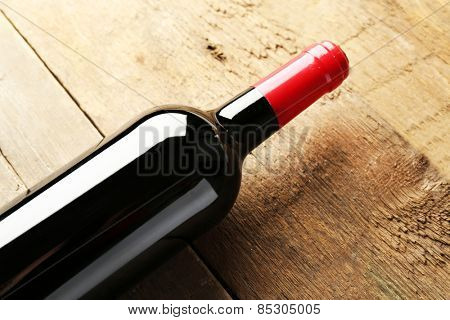 Glass bottle of wine on wooden table background