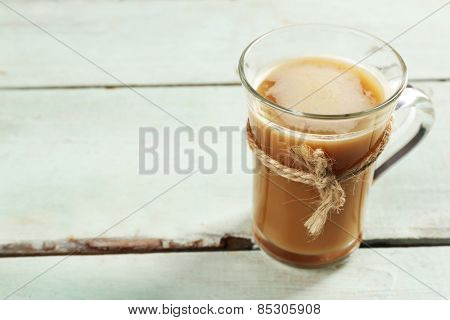 Glass cup of cocoa on color wooden planks background