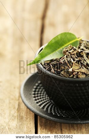 Green tea with leaf in cup on old wooden table
