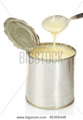 Tin can of condensed milk with spoon isolated on white