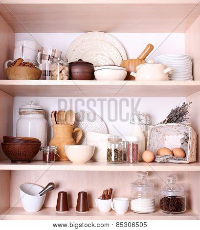 Kitchen utensils and tableware on shelves