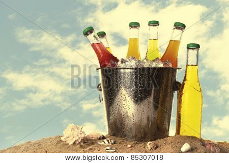 Bottles of tasty drink in metal bucket with ice on sand isolated on white