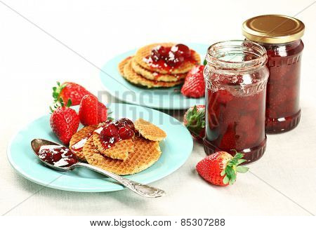 Wafers with strawberry jam and berries on plates on table close up