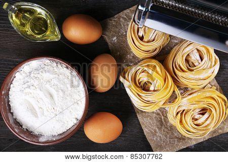 Preparing pasta by pasta machine on rustic wooden background