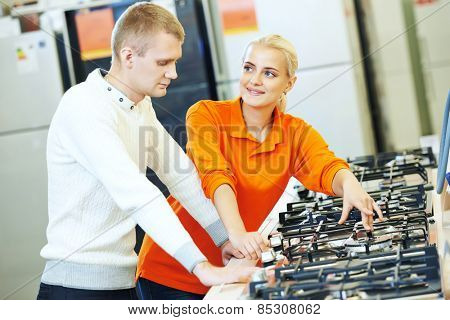 Young man choosing kitchen range cooker in home appliance shopping mall supermarket