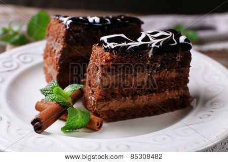 Tasty pieces of chocolate cake with mint and cinnamon on wooden table background