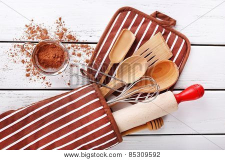 Set of kitchen utensils with cocoa in mitten on wooden background