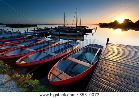 Boats By Pier At Harbor During Sunrise