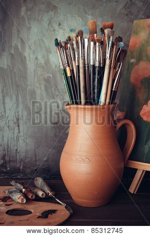 Paintbrushes In A Jug From Potters Clay, Palette, Paint Tubes And Painting In Artist Studio.
