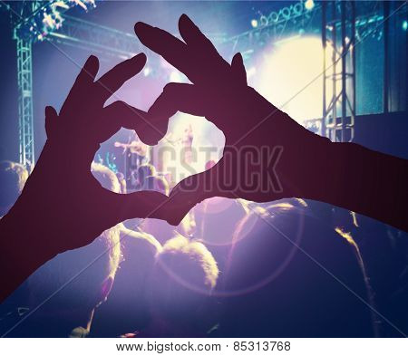 a person making a heart shape with their hands over a crowd of people at a concert toned with a retro vintage instagram filter effect