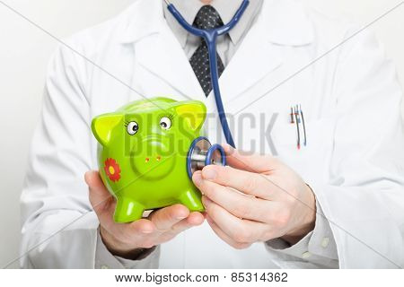 Medical Doctor Holding Stethoscope And Piggybank In Hand