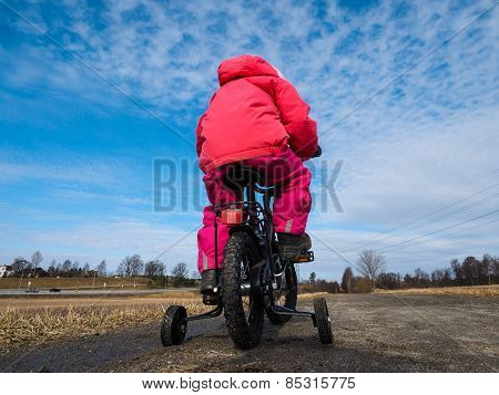 Little Girl Biker wearing ping under Blue Sky
