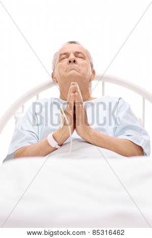 Senior patient praying in a hospital bed with an iv drip attached to his hand