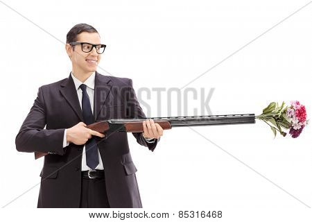 Businessman holding a rifle loaded with a bouquet of flowers isolated on white background