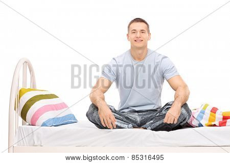 Young man in pajamas sitting on a bed isolated on white background