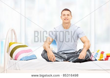 Young man in pajamas sitting on a bed at home