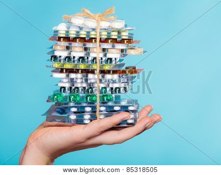 Hand Holding Stack Of Many Different Pills.