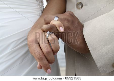 Wedding band and ring on fingers of newly weds