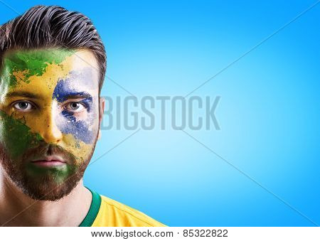 Man with his face painted with the Brazilian Flag on blue background