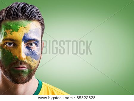 Man with his face painted with the Brazilian Flag on green background