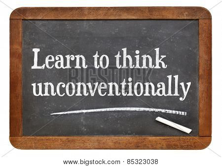 Learn to think unconventionally - motivational words  on a vintage slate blackboard