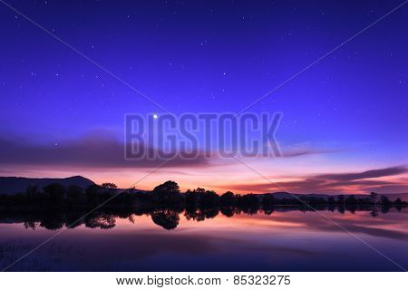 Beautiful Night Sky With Stars, Clouds And Reflections In The Wa