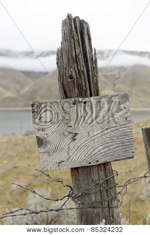 Old Wooden Fence Post And Rustic Sign