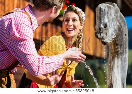 Couple at mountain hut drinking water from source well, scene set in the Alps with traditional clothing