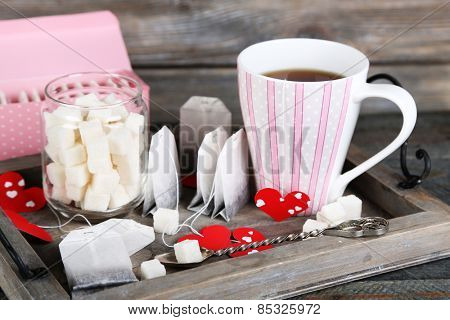 Heart shaped teabag tags, box and cup of tea on wooden background