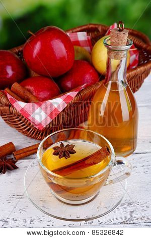Apple cider with cinnamon sticks and fresh apples in wicker basket on wooden table, on bright background